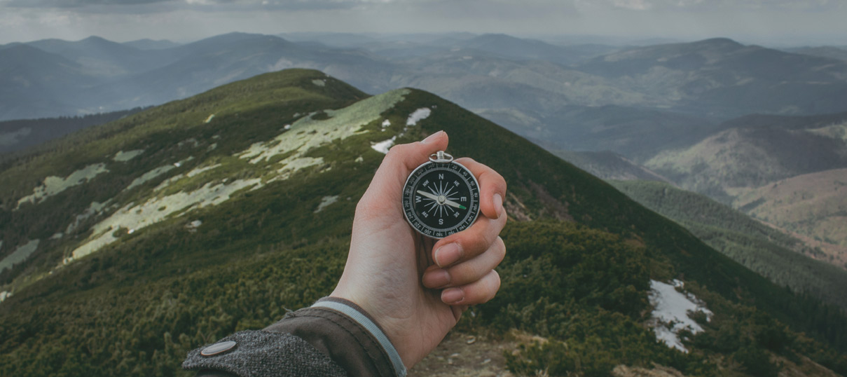 A compass being held in front of a scenic mountain view